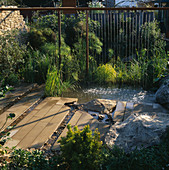 Water CURTAIN Feature FLOWING From A Rusty SCAFFOLDING POLE INTO Pool with ROCKS AND PAVING. Israel JUBILEE GARDEN. DES: DAVID STEVENS. CHELSEA