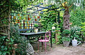 COURTYARD Garden: TABLE AND SEATS UNDER SHADY Pergola with STAINED GLASS Screen BEHIND. Designer: Jonathan BAILLIE