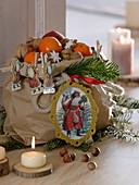 Papiertüte mit Nikolaus-Oblaten, gefüllt mit Mandarinen (Citrus), Nüssen
