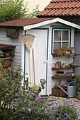 Kleines Gartengerätehaus mit Regal für Töpfe und Utensilien, Gießkanne