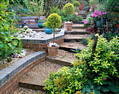WOODEN SLEEPERS EDGE STEPS THROUGH THE Garden with STANDARD CLIPPED TREES AND Old Garden TOOLS LINING THE PATH. ROBIN Green AND RALPH CADE'S SEASIDE STYLE Garden, LONDON.