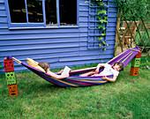 HARRIET AND Nancy MATTHEWS Relax IN A MULTI-COLOURED HAMMOCK. Behind IS THE Blue SUMMERHOUSE. Designer: Clare MATTHEWS