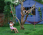 HARRIET AND Nancy MATTHEWS PLAY On THE Old TREE with Blue SUMMERHOUSE BEHIND. Designer Clare MATTHEWS.