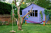 THE CHILDRENS PLAY AREA with Blue SUMMERHOUSE, BLACKBOARD, HAMMOCK, TURF CROCODILE AND Old TREE. DESIGN by Clare MATTHEWS