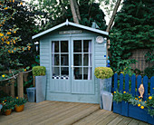 THE 'UPPER DECK' TERRACE with Blue SUMMERHOUSE, DECKING AND Blue DECORATIVE FENCING. ROBIN Green & RALPH CADE'S Garden, London