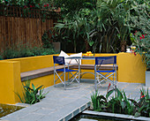 A PLACE TO SIT: Aluminium TABLE AND CHAIRS On Patio SURROUNDED by Yellow RENDERED WALLS with RAISED BEDS AND RILL. TRACHYCARPUS AND PHORMIUM FOLIAGE IN B / G . Designer Joe SWIFT