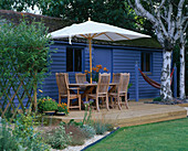 Blue SUMMERHOUSE with DECKING, TABLE, CHAIRS AND Parasol, BIRCH TREE TRUNKS, ORANGE LILLIES, HAMMOCK AND GRAVEL. Designer: Clare MATTHEWS