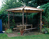 CROCODILE WOODEN BENCH by HUW Morris (LUSTY Garden FURNITURE COMPANY) STANDS BENEATH A RUSTIC POLE Pergola DESIGNED by Clare MATTHEWS