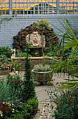 VIEW Along Garden PAST Box AND TRACHYCARPUS TO Water Feature Made of BRICK WALL AND BRIGHTON Pier GOD HEAD with SHELLS BACKED by ROCKS AND Blue WALL with TRELLIS. Designer ANDREW