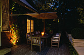 DECKED TERRACE with WOODEN TABLE, CHAIRS AND Parasol, LIT UP at NIGHT with CANDLES AND LIGHTS: LIGHTING by Garden AND Security LIGHTING