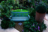 Circle of GRASS with Blue WOODEN BENCH AND TERRACOTTA Container with Box BALL. LISETTE PLEASANCE'S Garden, London
