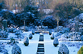 EASTLEACH HOUSE, Gloucestershire: THE RILL Garden COVERED IN SNOW with THUJA ORIENTALIS AUREA NANA AND SORBUS ARIA LUTESCENS