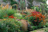 THE RILL Garden at EASTLEACH HOUSE, Gloucestershire: HELENIUM 'MOERHEIM BEAUTY' AND MONARDA 'SQUAW'