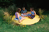 JASMINE, ANDY AND SHANA HICKS SIT On THE Yellow Circle of DECK SURROUNDED by BIDENS AUREA, HELICHRYSUM, STIPA TENUISSIMA AND Carex BUCHANANII: DESIGN: Clare MATTHEWS
