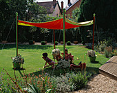 SHADE CANOPY: JOSHUA AND Nancy Relax I N DECKCHAIRS UNDERNEATH THE SHADE CANOPY On THE LAWN: Designer: Clare MATTHEWS