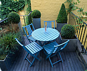ROOF Garden DESIGNED by STEPHEN WOODHAMS: DECKED TERRACE with Blue TABLE AND CHAIRS, Yellow PAINTED WALL AND Metal CONTAINERS PLANTED with Box
