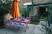 Blue Cafe CHAIRS, Pink WOODEN TABLE, Orange Parasol, DECKING AND GALVANISED TRAY PLANTED with SUCCULENTS: Designer: STEPHEN WOODHAMS