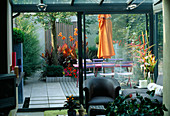 VIEW OUT of FLAT with Blue Cafe CHAIRS, Pink WOODEN TABLE, Orange Parasol, DECKING, Orange Canna AND GALVANISED TRAY PLANTED with SUCCULENTS: Designer: STEPHEN WOODHAMS