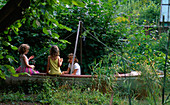 CHILDREN PLAYING IN an Old BOAT IN Rosemary PEARSONS Garden, READING