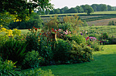 LAUNA SLATTERS Garden OXFORDSHIRE: LAWN AND BORDER with COUNTRYSIDE BEYOND