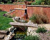 PETERSFIELD Garden WOODEN BRIDGE OVER STREAM with RENDERED WALL. Designer: Mark LAURENCE