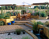 GRAVEL Garden with RENDERED CONCRETE WALL, Pool with SPOUT Water Feature, DECKING,Pergola, TABLE AND CHAIRS, Cream PARASOL. Designer: Mark LAURENCE