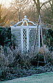 West Green HOUSE Garden, Hampshire: FROSTY BORDER IN Winter with A WOODEN TRIPOD IN Front of A White Ornamental SEAT IN THE WALLED Garden