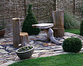 A PLACE TO SIT: WOODEN SEAT AND TABLE On STONE FLOOR. JOHN MASSEYS Garden, WORCESTERSHIRE