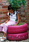 Designer: Clare MATTHEWS - FRAGRANT TREE SEAT - Girl SITTING On Pink PAINTED CAR TYRES PLANTED with A FIG TREE AND THYMES