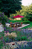 Designer Clare MATTHEWS: THE STONE TERRACE with Green OAK TABLE AND BENCHES AND Red Parasol SEEN From THE WALLED Garden