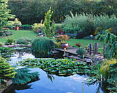 VIEW ACROSS THE LILY POND TO WOODEN PONTOON with STANDING STONES. Designer : JOHN MASSEY