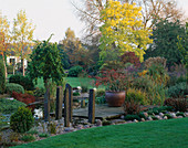 VIEW TOWARDS THE HOUSE with THE LILY Pool, WOODEN PONTOON AND STONE SCULPTURES. Designer: JOHN MASSEY