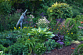 WOODCHIPPINGS, NORTHANTS: THE Old Orchard IN SPRING with Statue AND HOSTA. WOODLAND, SHADE, SHADY