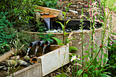 Water Feature: RILL SPILLING INTO A CIRCULAR STONE BASIN AND OUT AGAIN THROUGH THREE PIPES INTO ANOTHER RILL.WINGWELL NURSERY, Rutland