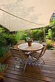 WOODEN DECKING with WOODEN TABLE AND CHAIRS, SHADE CANOPY, CANVAS. KATHY Taylor'S SMALL Town Garden, London
