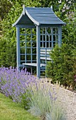 RICHARD JACKSONS GARDEN. DESIGNED by Clare MATTHEWS - GRAVEL PATH Beside LAWN with Blue WOODEN SUMMERHOUSE