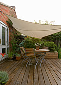 KATHY TAYLORS Garden, LONDON. SMALL GARDEN. A PLACE TO SIT: WOODEN TABLE AND CHAIRS On DECKED Patio / TERRACE with SHADE CANOPY OVERHEAD