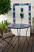 KATHY TAYLORS Garden, London: A PLACE TO SIT: MEDITERRANEAN STYLE TERRACE with MOSAIC TABLE, CHAIR, Water FEATURE.