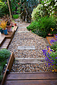KATHY TAYLORS Garden, London: VIEW Along GRAVEL PATH with SLEEPERS TO SHED COVERED by PHORMIUM AND Eucalyptus PAUCIFLORA SUBSP DEBEUZEVILLE