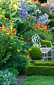 THE Old RECTORY, HASELBECH, NORTHANTS: White Metal CHAIR SURROUNDED by Box, Achillea AND KNIPHOFIA