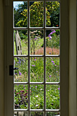Clare MATTHEWS HOUSE, DEVON. VIEW OUT of A DOOR IN THE SITTING ROOM TO THE Garden BEYOND