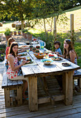 Clare MATTHEWS Garden, DEVON. Clare AND FAMILY SIT DOWN TO an Al Fresco LUNCH at THE TABLE. OUTDOOR DINING. Food, A PLACE TO SIT, EATING