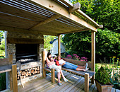 Designer Clare MATTHEWS: Devon GARDEN. Clare AND CHILDREN Relax On A WOODEN BENCH UNDER A PERGOLA. OUTDOOR OVEN. OUTDOOR KITCHEN