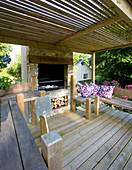 Designer Clare MATTHEWS: Devon GARDEN. OUTDOOR KITCHEN with DECKING, OVEN AND BENCHES with Purple AND White CUSHIONS