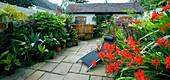 DARREN CLEMENT'S Garden, Staffordshire: COURTYARD with Hot TUB, Sunlounger AND CROCOSMIA 'LUCIFER'