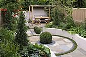 SMALL LOW MAINTENANCE Garden IN London DESIGNED by Charlotte ROWE. RAISED CONCRETE BEDS, Box BALLS IN PAVING, WOODEN Pergola, TABLE AND CHAIRS