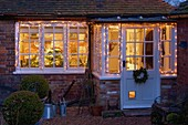 BOONSHILL Farm at CHRISTMAS. VIEW of THE KITCHEN From OUTSIDE with FAIRY LIGHTS On IN FROST. Designer LISETTE PLEASANCE