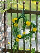 Kleines Herz aus Gras mit Löwenzahnblüten an rostigen Zaun gehängt