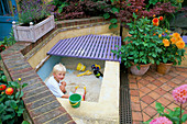 Patio with Robert PLAYING IN SANDPIT Made From Breeze BLOCKS AND RENDERED with PLASTER.SOFTWOOD WOODEN DECKING COVERS THE SANDPIT WHEN Not IN USE. DAHLIAS IN TERRACOTTA POTS