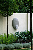 SANCTUARY Garden SPONSORED by MERRILL LYNCH at THE CHELSEA FLOWER Show 2002: DESIGNED by STEPHEN WOODHAMS: ONE of THE FIVE 'FACE' SCULPTURES by STEPHEN Cox Beside CLIPPED SANTOLINA